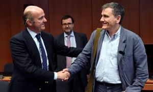 Greek finance minister Euclid Tsakalotos (right) has finally persuaded eurozone creditors to unlock vital bailout cash.