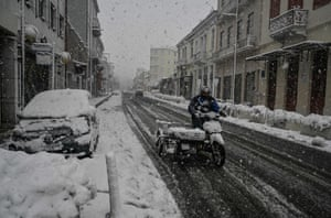 A man rides a motorcycle in central Athens during a rare heavy snowfall in the city
