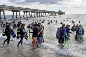 Florida, US. Divers attempt to break the world record for the largest underwater cleanup at the Deerfield Beach International Fishing Pier. The record was broken with 633 divers taking part