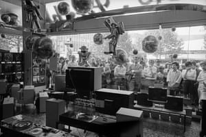 Berliners stand in front of a TV shop and look through the window of a space-themed TV shop to watch the start of the Apollo 11 space missio