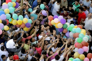 People grab balloons distributed after prayers in Cairo, Egypt