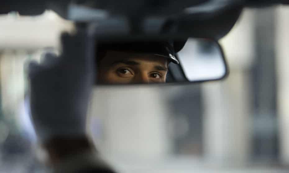 A chauffeur looks in his mirror