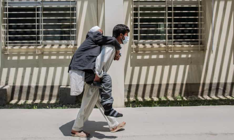 A patient is carried by a relative to the Afghan-Japan hospital in Kabul