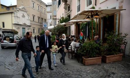 A Syrian family walks with a member of the Sant'Egidio Roman Catholic charity
