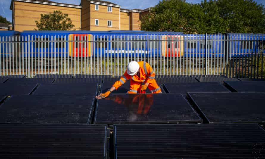 A worker cleans an array of solar panels near Aldershot Railway Station as part of the first UK project to power a railway with solar power generated electricity.