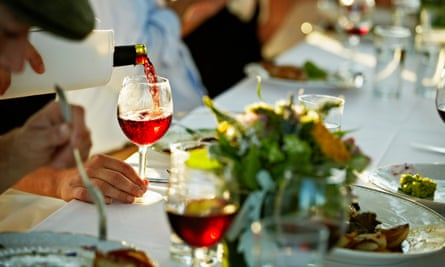 Red wine being poured into glass at a dinner table