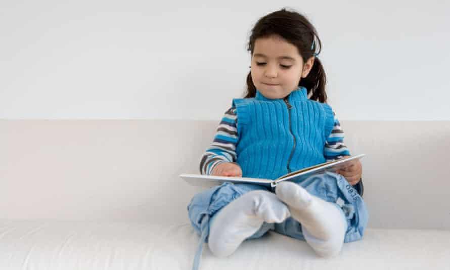 Little girl pretending to read a book