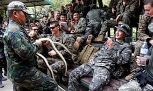 South Korean and US Marines listen to an instructor tell them how to catch a snake during a joint military exercise