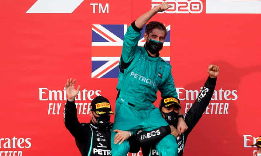 Lewis Hamilton (right) celebrates on the podium with second placed teammate Valtteri Bottas (left) and a Mercedes F1 team mechanic.