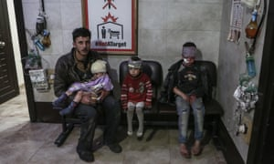 A man and three children, who were wounded in air strikes carried out by warplanes of the Syrian government, sit at a makeshift hospital