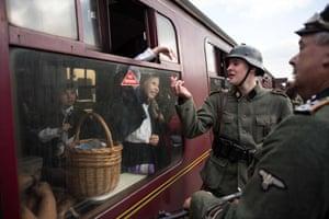 Second world war re-enactors dressed as German soldiers speak to train passengers at Levisham station.