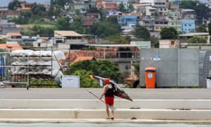 A man holds his kayak with a favela in the background during the Rio 2016 Olympic Games doubles kayak canoeing test in Rio de Janeiro