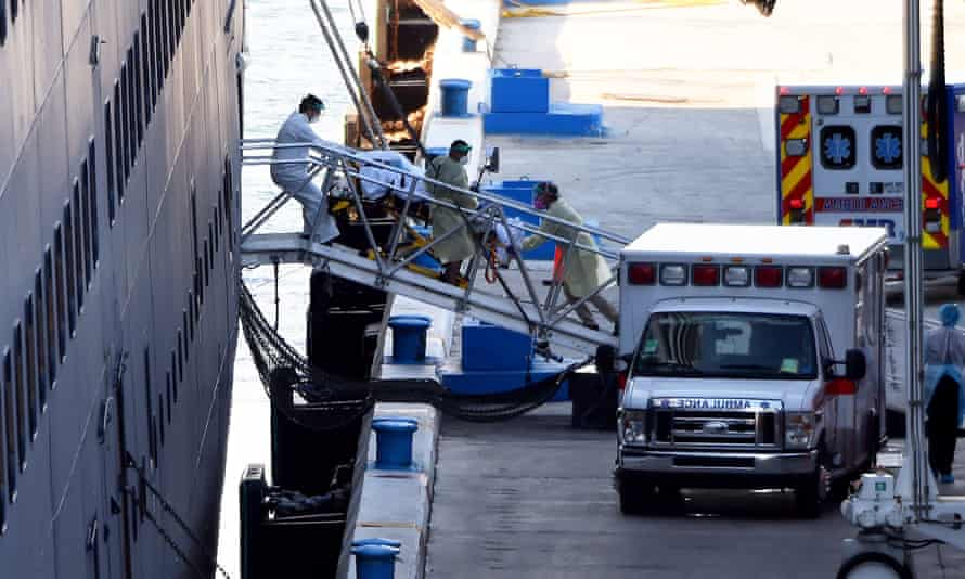 Medical workers guide a patient on a stretcher from the Zaandam cruise ship into a waiting ambulance in Fort Lauderdale, Florida.