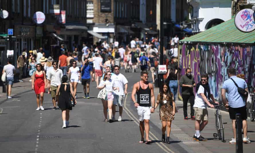 People enjoy the warm weather in east London's Broadway market on Saturday.