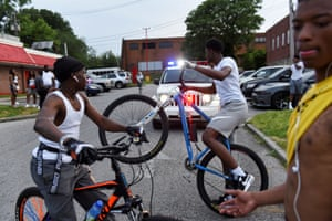 Young people ride their bikes near a police car at a parking lot in Baltimore.
