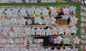 A woman hangs on a paper note to wish for her child's success in the college entrance exams at the Jogyesa Buddhist temple in Seoul, South Korea, Thursday, 3 December 2020.