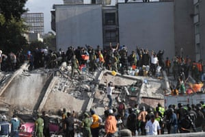 Rescuers, firefighters, police, soldiers and volunteers remove rubble and debris from a flattened building in search of survivors.