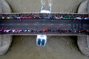 A boat passes underneath Tower Bridge as runners approach the halfway mark