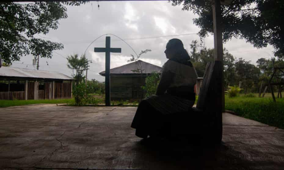 Indigenous woman pictured in silhouette before a large cross