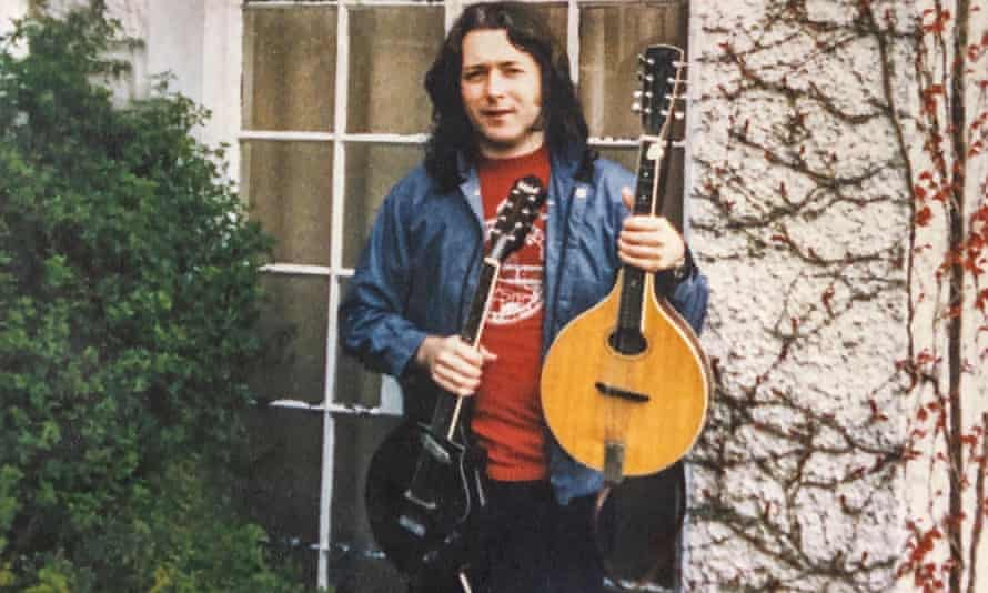 The musician Rory Gallagher with an acoustic octave mandola and a solid electric mandolin, made by Christopher Eccleshall