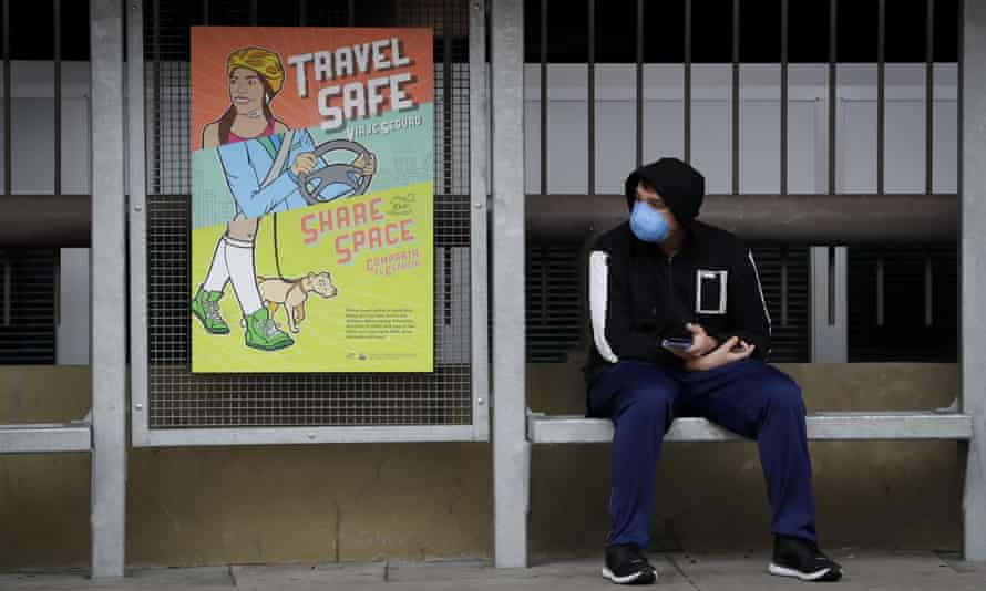 A bus rider wearing a face mask waits at a stop on 16 March 2020.
