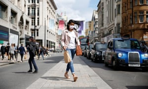 A shopper wearing a face covering crosses the street in London, England. The UK has reported a further 113 new Covid-linked deaths.