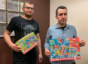 Igroland employees Nikita Filipov and Mikhail Bober holding the board game Our Guys in Salisbury.