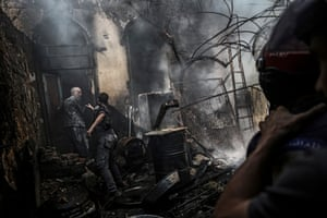 Firefighters extinguish a fire following an airstrike by forces loyal to the Syrian government in the rebel-held area of Douma