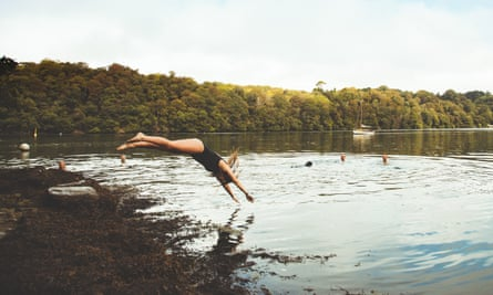 Woman diving into river at Thera-Sea retreat in Cornwall