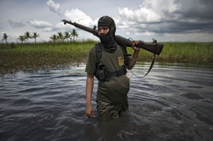Maguindanao, Philippines A member of the Moro Islamic Liberation Front rebel group walks through marshland, Maguindanao, Philippines