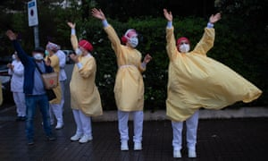 Heathcare workers wearing face masks and protective suits as they battle coronavirus acknowledge applause outside the Hospital de Barcelona on April 13, 2020.