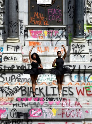 Ballerinas Kennedy George, 14, and Ava Holloway, 14, pose in front of a monument of the Confederate general Robert E Lee after Virginia's governor, Ralph Northam, ordered its removal, in Richmond, Virginia, on 5 June