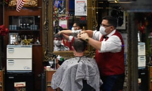 A barber and his customer wearing masks.