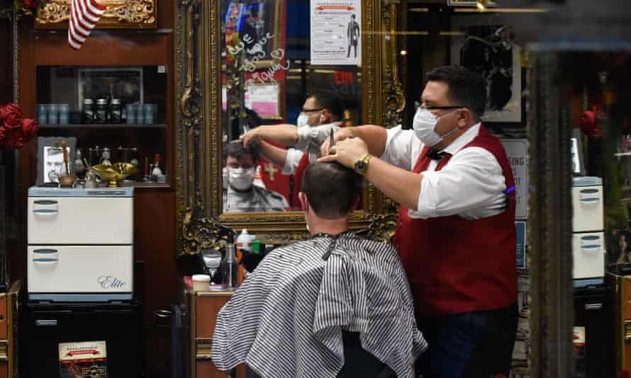A barber and his customer wearing masks.