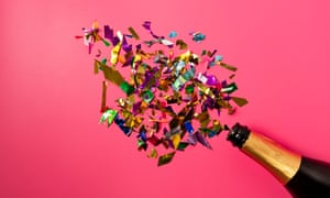 Champagne bottle with confetti on a pink background