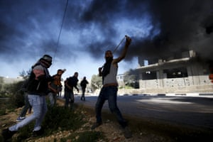 A Palestinian protester uses a slingshot to hurl stones at Israeli troops