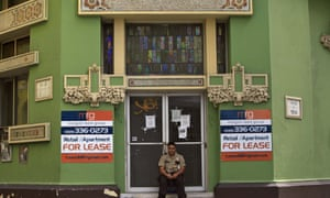 A private security guard sits in front of a closed-down business in the colonial district of Old San Juan, Puerto Rico.