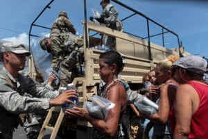 Soldiers of Puerto Rico's national guard distribute relief items to people in San Juan