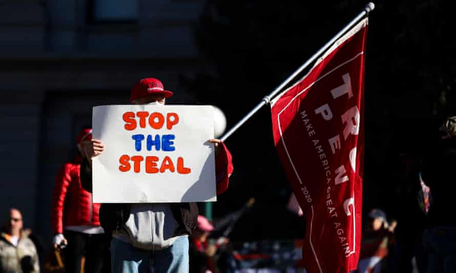 A Trump supporter holds a 'Stop the Steal' sign in Denver, Colorado, on 6 January.