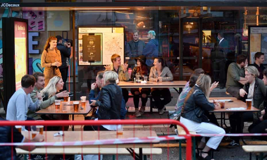 Customers drink in converted bus shelters in Manchester.