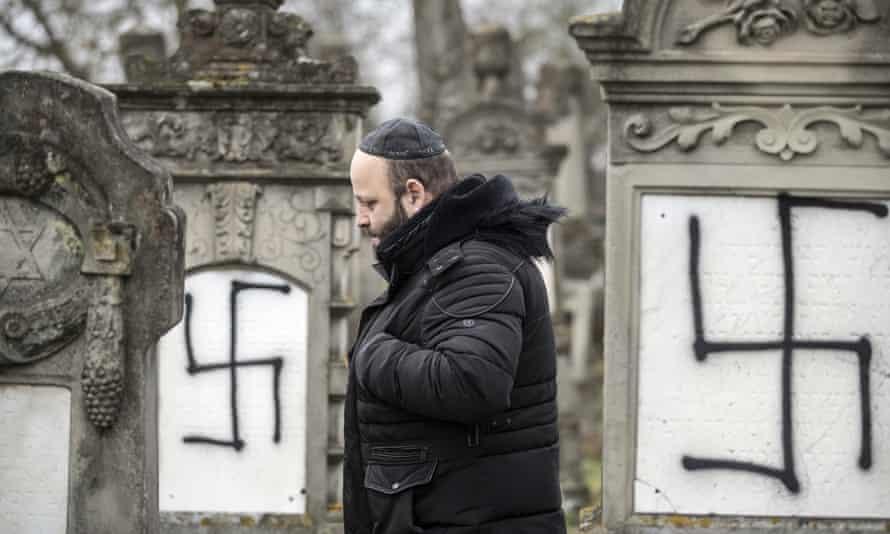A man walks among defaced gravestones at the Jewish cemetery of Herrlisheim, near Strasbourg, eastern France.