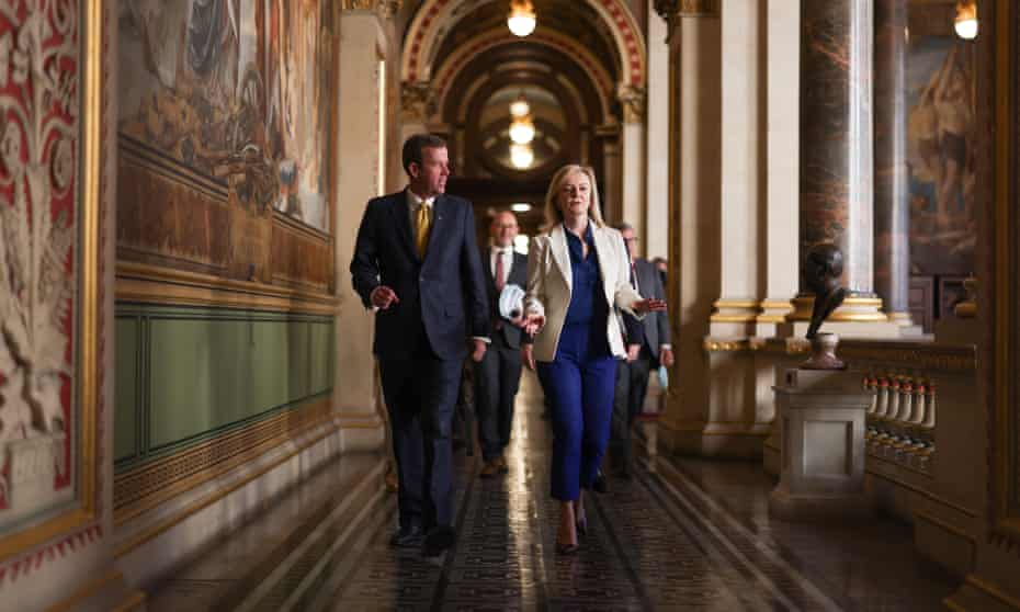 Dan Tehan and Liz Truss walking together through an impressive pillared corridor in the Foreign Office