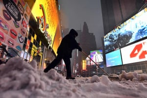 A man clears snow from the street in Times Square in New York