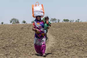 In India's Lalitpur district, Avadrani, a widow, has been unable to find work during the drought. She walks across the parched landscape with her son, Somath, to collect an emergency relief package that will help feed her family for a month. More than 300 million people in India have been affected by the two-year drought