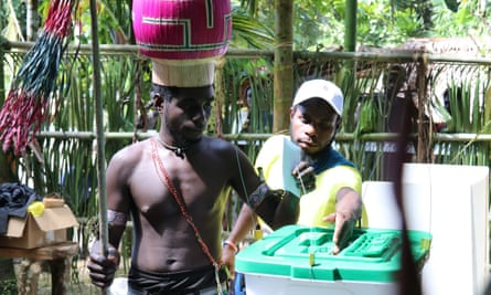 a man puts a voting ballot in a plastic tub in Bougainville