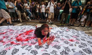 A performance artist makes her mark about Chinese rule on the streets of Hong Kong yesterday.
