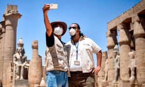 Mask-clad tour guides pose together for a selfie at the colonnade of the ancient Temple of Luxor in Egypt, as the country eases coronavirus restrictions.