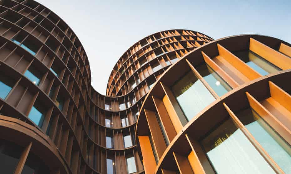 A view looking up at Axel Towers - round towers made of yellow shiny metal and glass