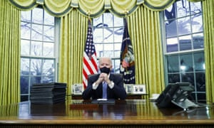 Biden signs executive orders in the Oval Office.