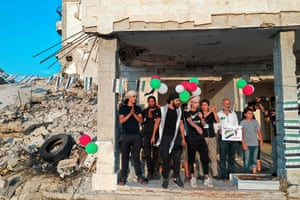 Ariha, Syria: Chanters lead an anti-government demonstration amid destroyed buildings in Idlib province